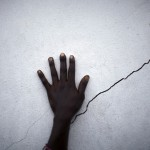 hand near a crack on a wall