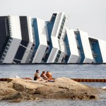 Tourists sunbathing next to the Costa Concordia
