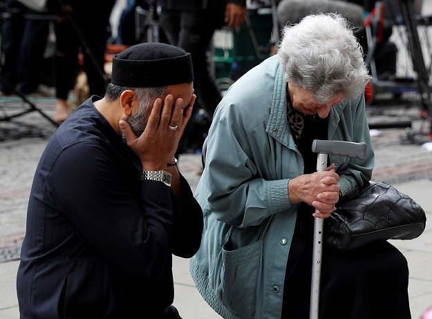 A Jewish woman named Renee Rachel Black and a Muslim man named Sadiq Patel react next to floral tributes in Albert Square in Manchester, Britain. PHOTO: REUTERS