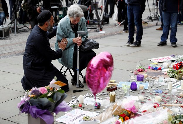 A Jewish woman named Renee Rachel Black and a Muslim man named Sadiq Patel react next to floral tributes in St Ann's Square in Manchester, Britain. PHOTO: REUTERS
