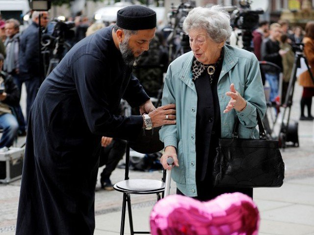 A Muslim man named Sadiq Patel comforts a Jewish woman named Renee Rachel Black next to floral tributes in Albert Square in Manchester, Britain. PHOTO: REUTERS