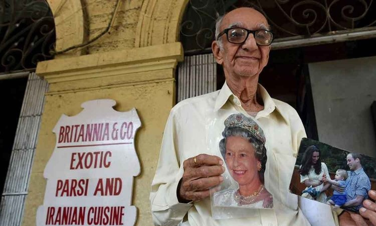 Boman Kohinoor posed with photos of Queen Elizabeth, and the Duke and Duchess of Cambridge outside his restaurant in Mumbai. Photo: AFP